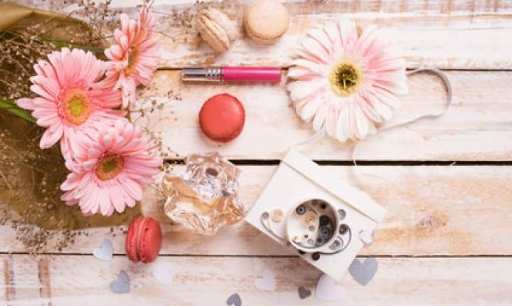 pink flowers and multi colored macarons on wooden table