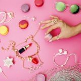 woman hands holding macaroons with lot of girl stuff on pink background, girls accessories concept